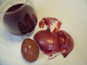 I used the dried skins of 3 red onions, 1 cup of boiling water and 1 tablespoon vinegar. The egg sat in the solution for several hours.